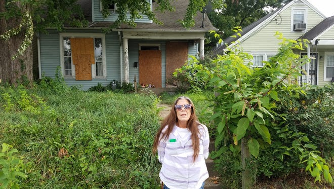 Reinella Kirilova, mother of William Young, stands in front of the house where her son was shot and killed.
