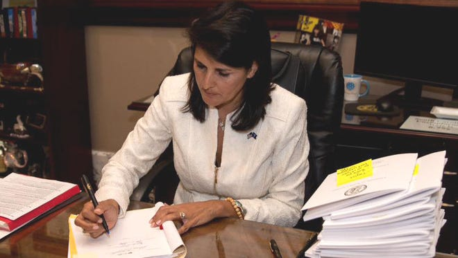 Gov. Nikki Haley signs a bill firing the SC State University trustees.