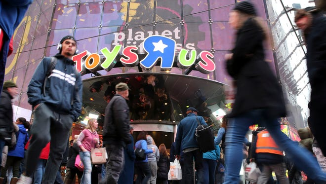 Visitors to New York's Times Square walk past the Toys R Us store, Wednesday, Dec. 30, 2015. Fourteen years after it began wowing millions of tourists with its indoor 60-foot Ferris wheel and a growling 20-foot Tyrannosaurus, the giant Toys R Us flagship store in Times Square closes its doors Wednesday. (AP Photo/Mary Altaffer)