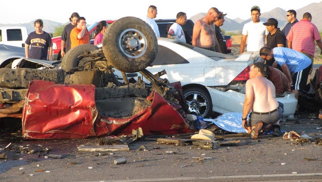 Bystanders to a fatal accident on Interstate 10 near Picacho Peak in which five people were killed on March 29, 2014.
