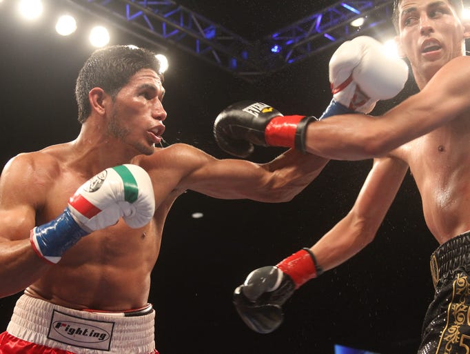 Angel Osuna, in red trunks, starts to dominate the pace of the fight early on against Hugo Centeno Jr. during their 10 round fight at Fantasy Springs Resort Casino on December 13, 2014. In this photo Osuna lands a left hook early in the fight.