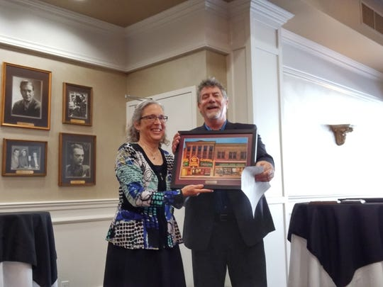Outgoing board member and Executive Committee Treasurer Patty Huettl (left) receives a framed print of the Capitol Civic Centre from Executive Director Matthew Schliesman.