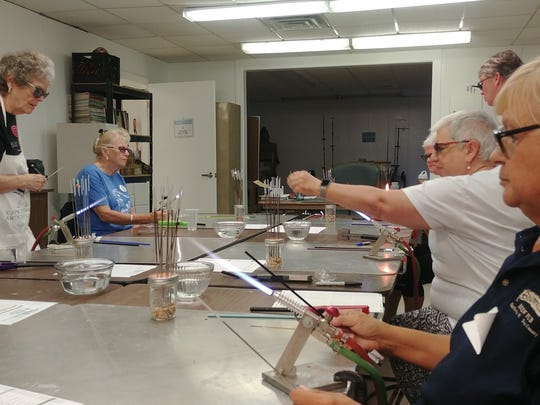 Class members get their flames going during a bead-making seminar at the Cape Coral Arts Studio.