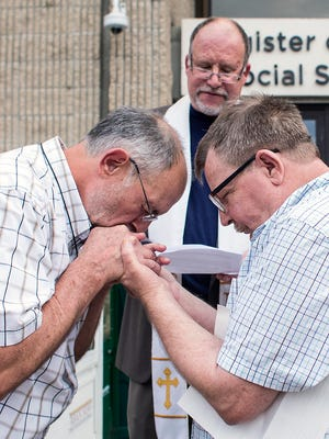 Bruce Mashburn, left, and Russ Rhymer hold hands as Rev. Joe Hoffman marries them on the steps of the Buncombe County Register of Deeds office in  this 2014 photo.