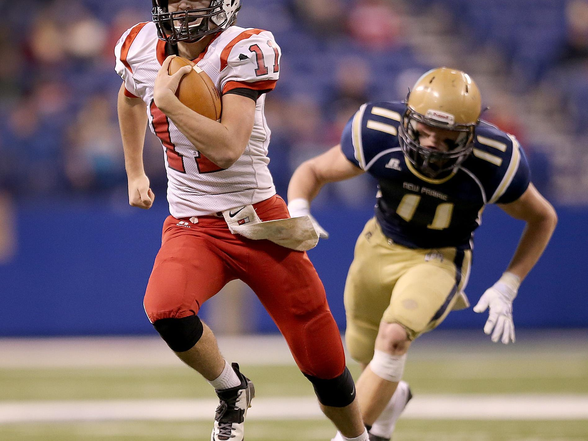 New Palestine's QB Alex Neligh runs by the New Prairie's defense for a touchdown in the first half of their game.The New Palestine Dragons took on the New Prairie Cougars in the IHSAA Class 4A State Football Championship game Friday, November 28, 2014, afternoon at Lucas Oil Stadium.
