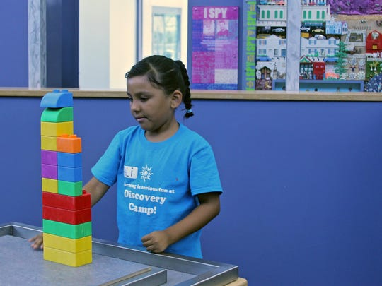 A summer camp participant builds a tower using plastic blocks, Monday, at the Children's Discovery Museum in Rancho Mirage.