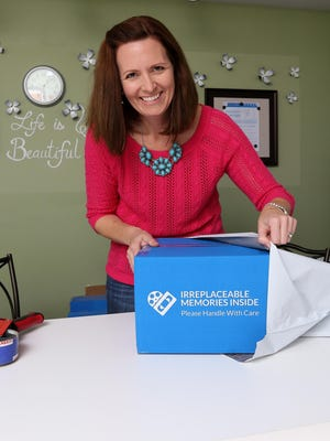 Legacy Maker Kris LeDonne readies a package of a customer's family memories to send to Legacy Republic's memory factory.