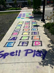 Hopscotch and other playful elements incorporated into the design of a Main Street sidewalk in the city of Rochester.