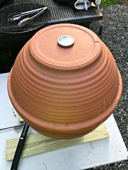 A thermometer is inserted in the top drainage hole to monitor the temperature of the smoker.