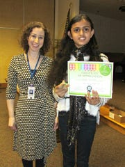 """Aanya Srinivasan, a fifth-grader at Eisenhower Intermediate School in Bridgewater, received her first-prize certificate (grades 3-5) for """"Monster Mash."""" She is pictured with Rebecca Klein, youth services librarian at the Bridgewater Library."""