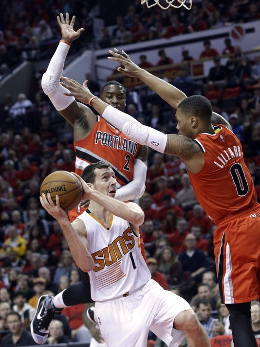 Phoenix Suns guard Goran Dragic, from Slovenia, left, looks for an opening to the basket against Portland Trail Blazers guard Damian Lillard, right, and teammate Wesley Matthews during the first half of an NBA basketball game in Portland, Ore., Thursday, Feb. 5, 2015.  (AP Photo/Don Ryan)