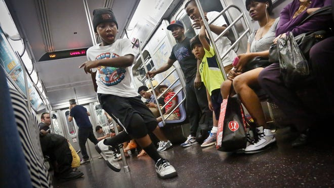 Marc Mack, 8, a member with the dance troupe W.A.F.F.L.E., performs on a subway in New York.