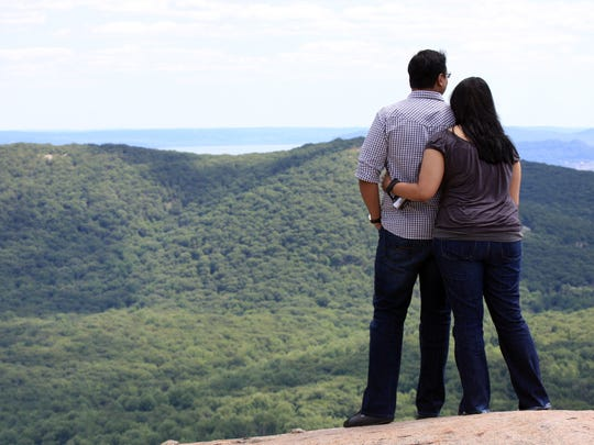 A couple take in the views from Perkins Tower at Bear Mountain State Park.  ( Carucha L. Meuse  / The Journal News )