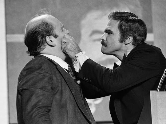 """FILE - In this Dec. 2, 1977 file photo, actor Burt Reynolds, right, pinches the cheeks of comedian Dom Deluise during a roast of Reynolds in Atlanta. Reynolds, who starred in films including """"Deliverance,"""" """"Boogie Nights,"""" and the """"Smokey and the Bandit"""" films, died at age 82, according to his agent. DeLuise died on May 4, 2009 at age 75. (AP Photo/Steve Helber, File)"""