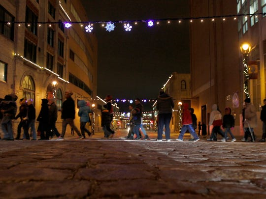People walk cross State St. amid the Miller Valley Holiday Lites Show, which runs through Saturday.