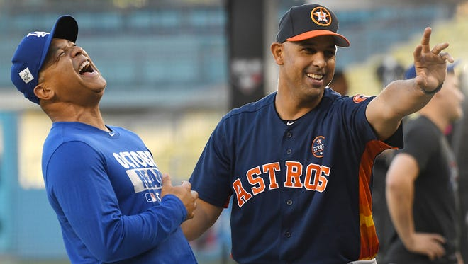 \Los Angeles Dodgers manager Dave Roberts (30) talks with Houston Astros bench coach Alex Cora (26) during workouts prior to game one of the World Series at Dodger Stadium. \
