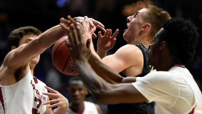Vanderbilt Commodores guard Riley LaChance (13)  struggles for the ball with Arkansas guard Dusty Hannahs (3) and forward Adrio Bailey (2) in the first half of their game in the 2017 SEC Men's Basketball Tournament at Bridgestone Arena Saturday, March 11, 2017 in Nashville, Tenn.