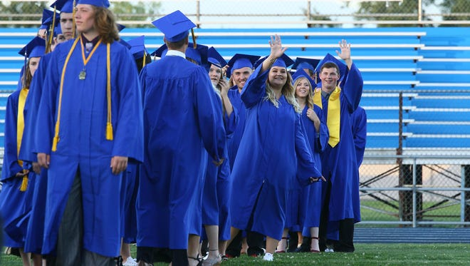 The graduates wave to families and friends while waiting for the procession at the beginning of the commencement on Thursday night.
