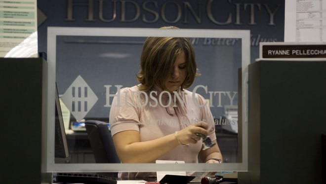 New Jersey's Hudson City Savings Bank branches likely will be converted to M&T Bank branches early next year. A Hudson City teller works in this 2010 file photo.