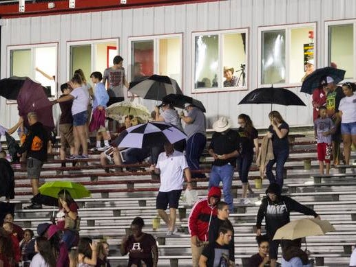 Fans leave the stands after a lightning delay was called before the start of the Riverdale vs. North Fort Myers high school football game on Friday night. The game was already delayed an hour and a half due to lightning.
