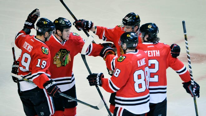 Chicago Blackhawks center Jonathan Toews (19), center Andrew Shaw (65), center Patrick Sharp (10), defenseman Duncan Keith (2) and right wing Patrick Kane (88) celebrate Shaw's goal during the first period against the Ottawa Senators at the United Center.