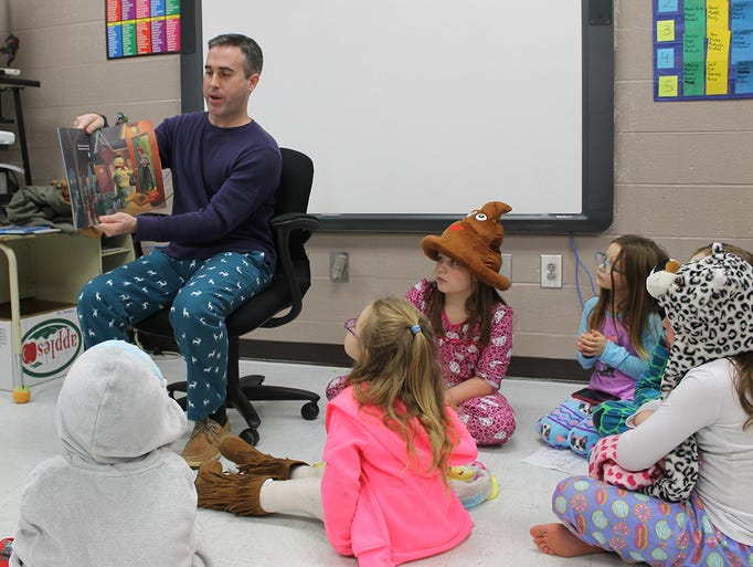 Pleasant View Police Officer Adam Wright reads a book