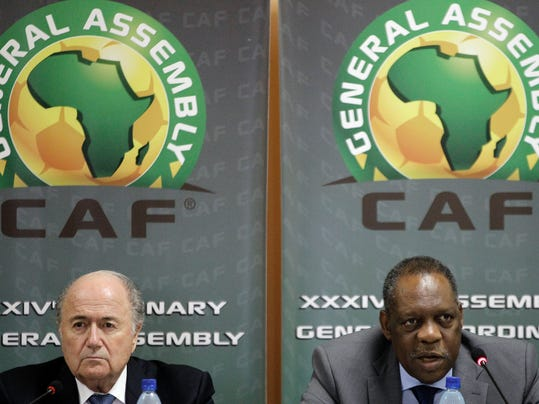 """FILE - This is a Friday Feb. 10, 2012 file photo of  Confederation of African Football President Issa Hayatou, right, speaks as FIFA President Sepp Blatter, left, looks on during a joint press conference in Libreville, Gabon. FIFA vice president and African football head Issa Hayatou  denied allegations Sunday June 1, 2014  made against him by British newspaper The Sunday Times that he received favors for voting for Qatar to host the 2022 World Cup.  In a statement late Sunday night, the Confederation of African Football called the corruption allegations against its president """"fanciful"""" and """"ridiculous.""""  (AP Photo/Themba Hadebe, File)"""