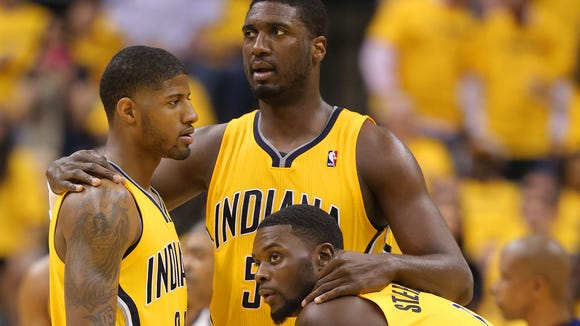 Indiana Pacers Paul George, Roy Hibbert and Lance Stephenson gather on the court.