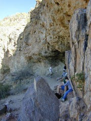 Hikers rest in the shade of the Wind Cave, a shallow