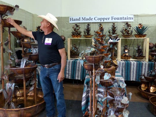 Roberto Marquez of Copper Fountains based in Tucson, Ariz., checks out one of his handmade fountains.