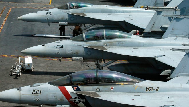 In this March 3, 2017 file photo, a row of F-18 fighter jets are shown on the deck of the U.S. Navy aircraft carrier USS Carl Vinson off the disputed South China Sea.