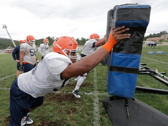 UTEP defensive lineman Mike Sota hits the sled during Wednesday's practice at Camp Ruidoso before the 2016 season.