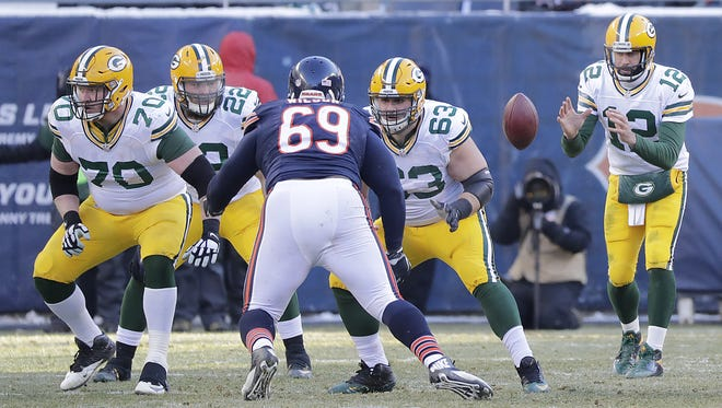 Green Bay Packers quarterback Aaron Rodgers (12) takes the snap as center Corey Linsley (63), fullback Aaron Ripkowski (22) and guard T.J. Lang (70) block against the Chicago Bears at Soldier Field.