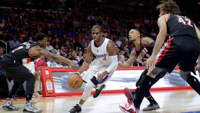 Los Angeles Clippers' Chris Paul, center, drives past Portland Trail Blazers' Wesley Matthews, left, and Damian Lillard as Trail Blazers' Robin Lopez, right, watches during the first half of an NBA basketball game Saturday, Nov. 8, 2014, in Los Angeles.