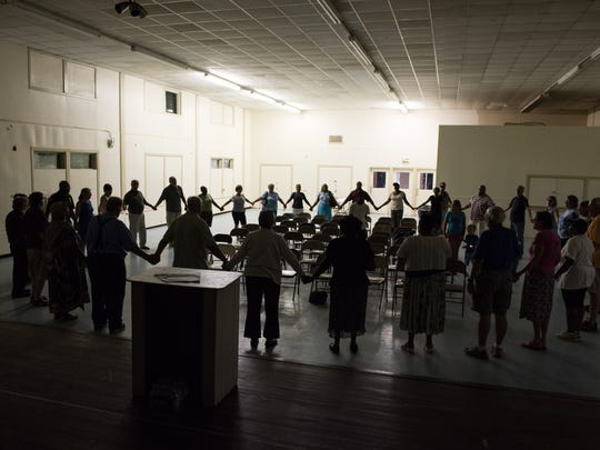 Community members hold hands in a circle during a community