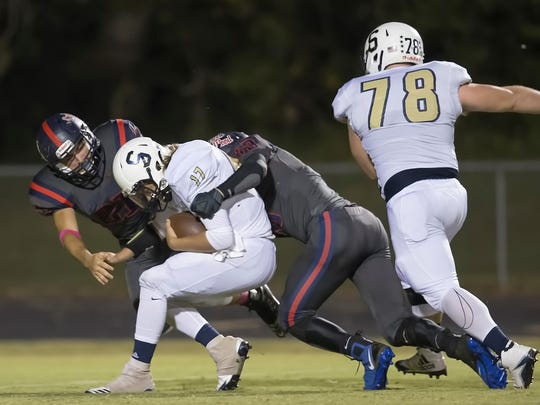 Sycamore quarterback Jerymiah Ivey is sacked by Creek