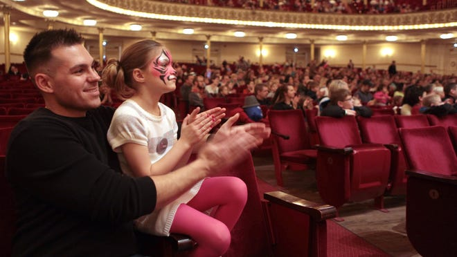 Gordon Green of Madeira and his daughter, Isabella, 7, applaud a circus performance at Music Hall during the Macy's Arts Sampler in 2015.
