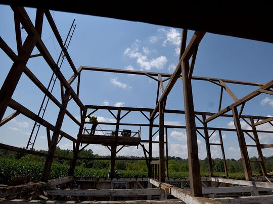 Workers from Ohio Valley Reclaimed Wood work on the Kisling Barn outside Lexington as it is carefully disassembled.