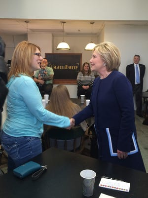 Hillary Clinton, right, greets a patron at 8 Sisters Bakery in Marion, Ohio, on Sunday, March 13, 2016.