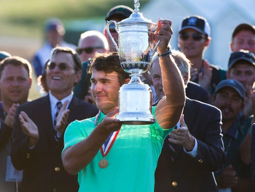 U.S. Open champion Brooks Koepka hoists the trophy