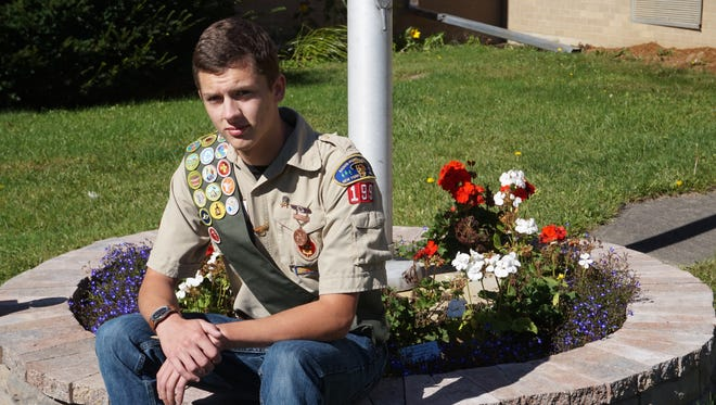 Devin Baldwin Reitz sits next to his completed flagpole flower planter, which served as his Eagle Scout project.