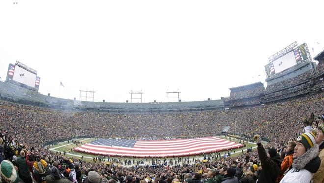Fans watch the fly over during Sunday's NFC divisional playoff game between the Green Bay Packers and the Dallas Cowboys at Lambeau Field.