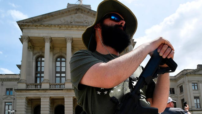 Andrew Norris, of Monroe, Ga.,participates in a gun-rights rally at the state capitol, Saturday, April 14, 2018, in Atlanta.  About 40 gun rights supporters have gathered for one of dozens of rallies planned at statehouses across the U.S.