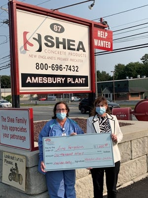 Amesbury resident Anne Ferguson, left, is presented with her $1,000 Grand Prize check from Brenda Stratis of Shea Concrete, right.