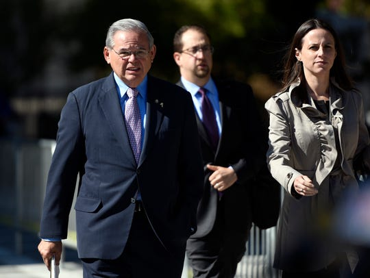 U.S. Sen. Bob Menendez, left, leaves court in Newark
