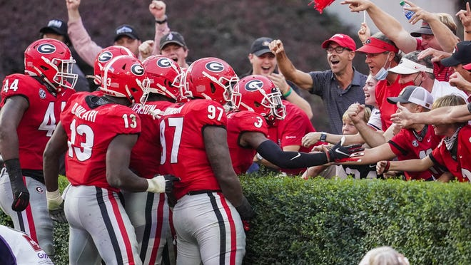 Oct 10, 2020; Athens, Georgia, USA; Georgia Bulldogs players react with fans in the end zone after linebacker Monty Rice (32) (in crowd of players) returns a  fumble for a touchdown against the Tennessee Volunteers during the second half at Sanford Stadium. Mandatory Credit: Dale Zanine-USA TODAY Sports