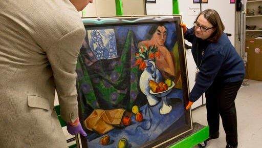 In this Friday, Nov. 18, 2016, photo, Karen Papineau, right, and Kurt Sundstrom work to turn around a painting by German artist Max Pechstein in Manchester, N.H. The rare double-sided painting is part of a new exhibit at the Currier Museum of Art.