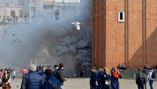 Smoke rises in famous St. Mark Square in Venice, Italy, Friday, March 17, 2017. News reports say thieves attempting to rob a jewelry store in Venice's St. Mark's Square set off panic among tourists when they ignited smoke bombs to cover their movements.