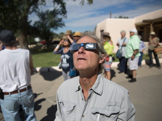 Tim Richards of Durango, Colo., watches the partial eclipse, Monday during a viewing event at the Aztec Ruins National Monument in Aztec, N.M.
