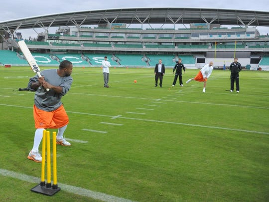 Bears linebacker Brian Urlacher, far right, bowls the ball to linebacker Lance Briggs during a cricket game at practice in London.